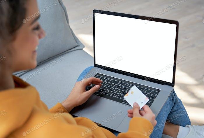 Happy hispanic female customer holding credit card paying online on laptop.