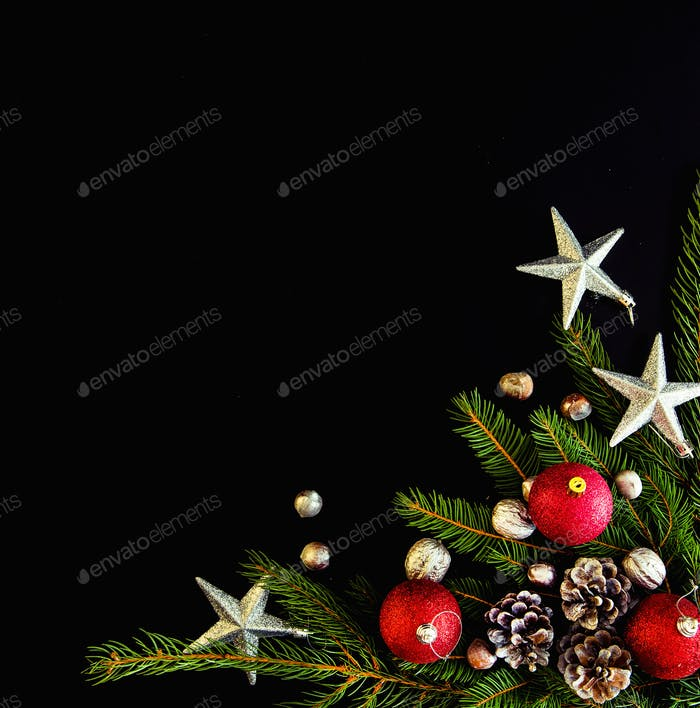 Christmas background with balls, stars, nuts, pine cones, fir tree branches on black. Space for text