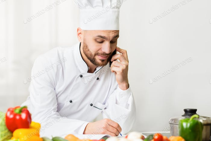 Male Chef Talking On Cellphone Taking Notes Standing In Kitchen