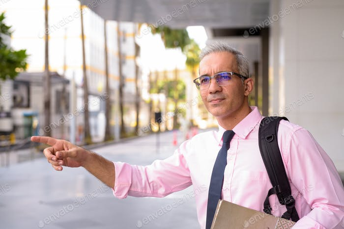 Handsome Persian businessman with backpack hailing cab outside modern building