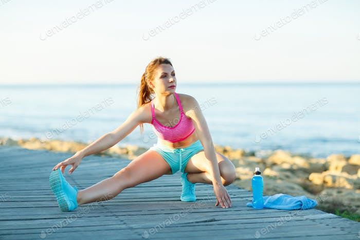 Sporty woman stretching before running or exercising by the sea