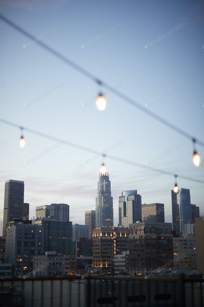 View Of Los Angeles Skyline At Sunset  With String Of Lights In Foreground