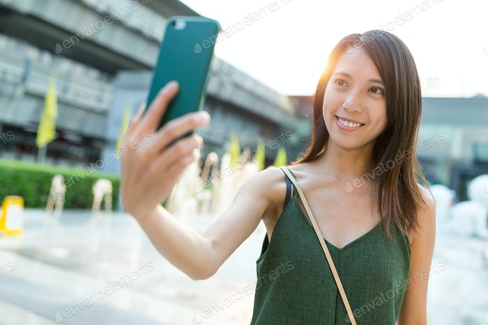 Woman taking selfie by mobile phone at street