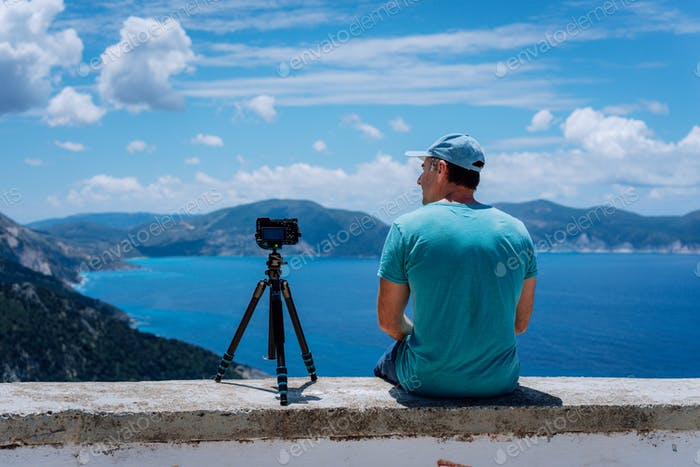 Summer holiday visiting Greece. Male freelance photographer enjoying capturing time lapse moving