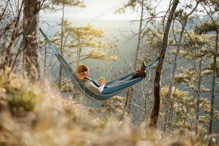 Junge glückliche Mann entspannt in Hängematte auf dem Berg liegend.