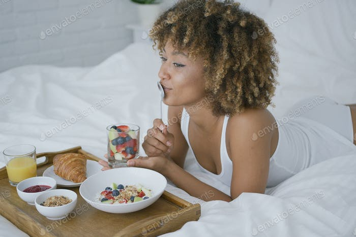 Dreaming woman having sweet meal in bed