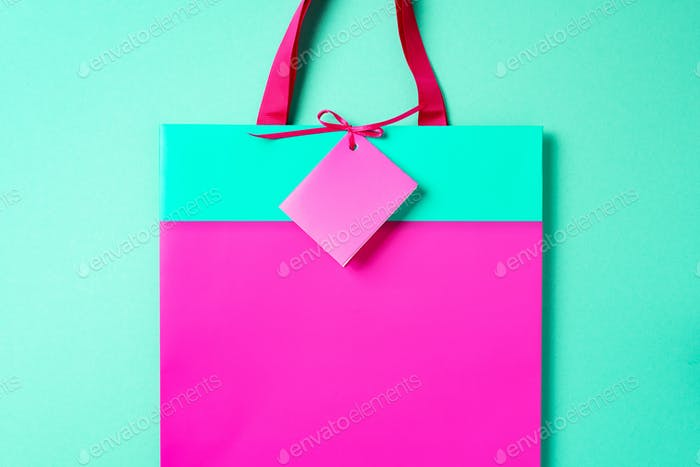 Black friday sale concept. Top view of pink and turquoise paper shopping bag on trendy green