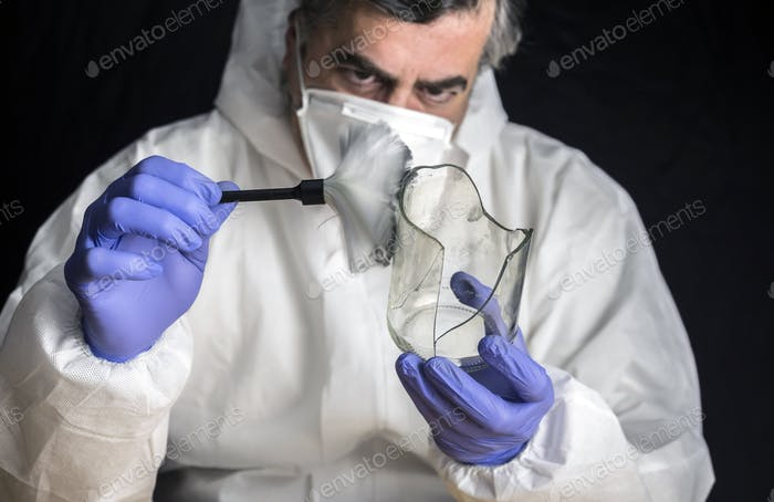 Expert Police get fingerprints from a broken glass bottle in Criminalistic Lab, conceptual image