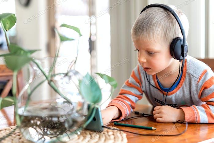 Kleiner Junge wares Kopfhörer und spielen das Handy