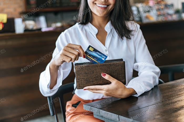 Accepting credit cards from a brown purse to pay for goods on coffee orders.