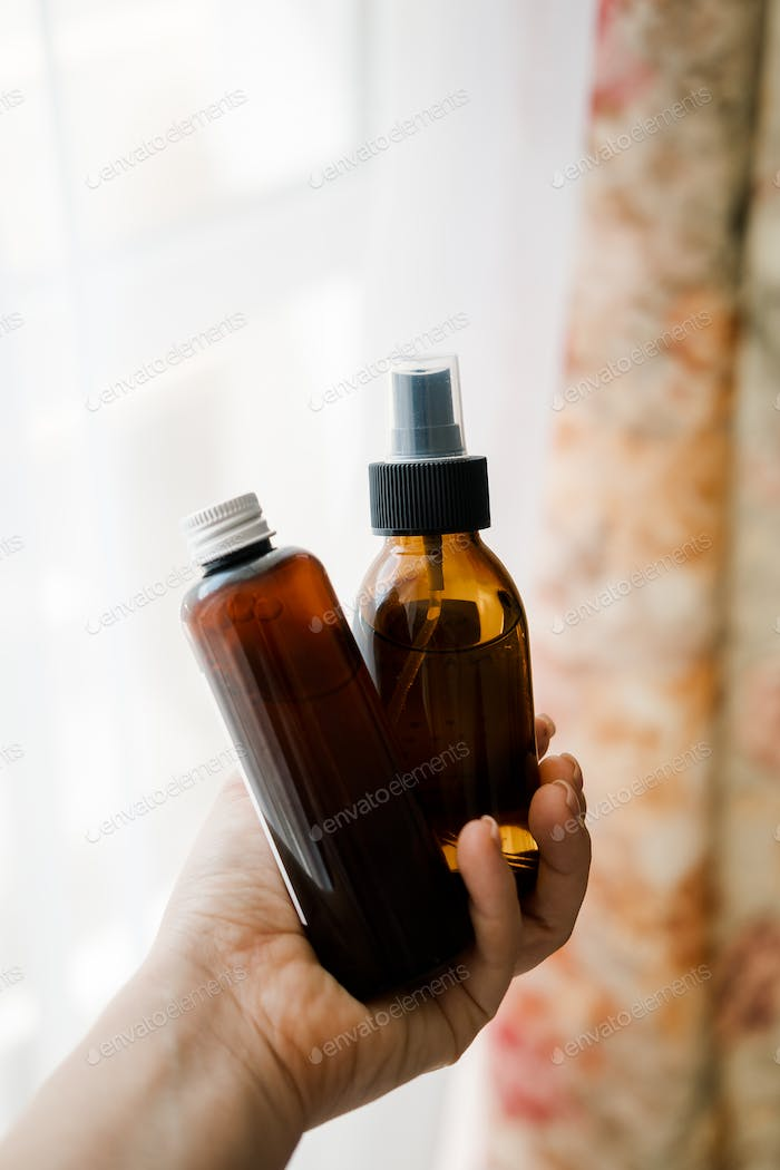 Two cosmetic bottles in woman's hands