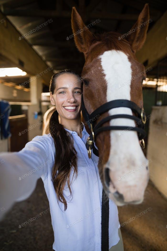 Portrait of female vet standing by horse