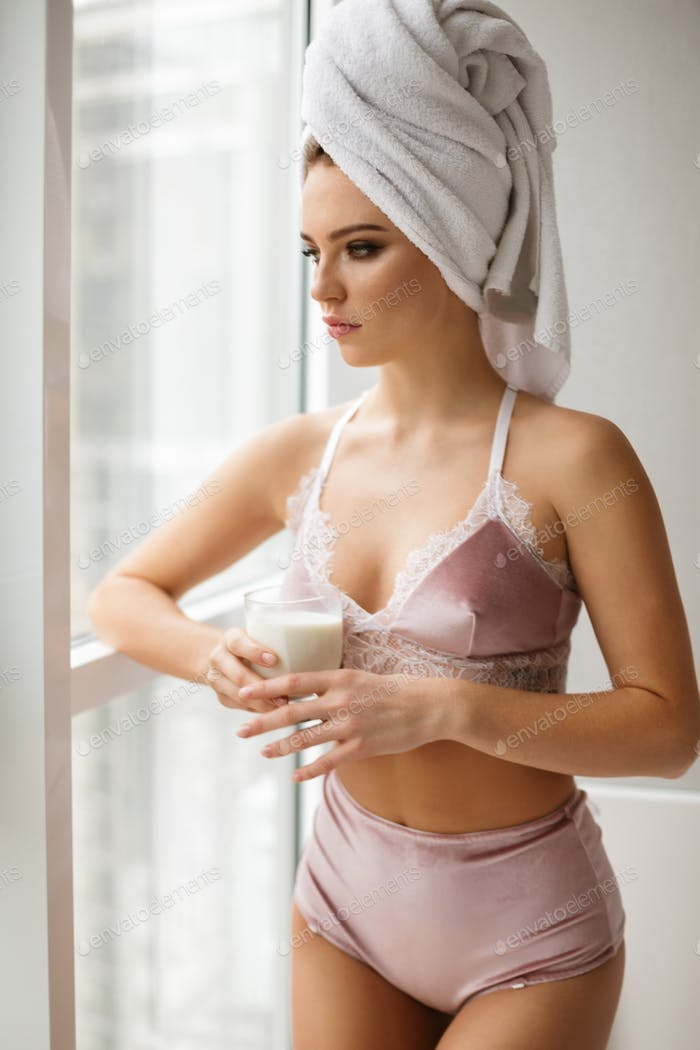 Lady standing with towel on her head near window thoughtfully looking aside with glass of milk