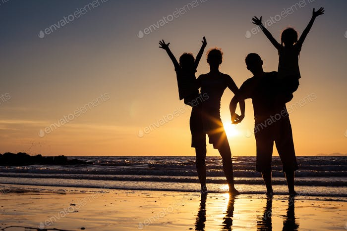 Silhouette of happy family who standing on the beach at the suns