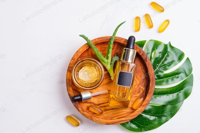 Kosmetische Flasche mit Öl oder Hyaluronsäure und Glas mit Maske für das Gesicht, Omega-3 Gelkapseln auf