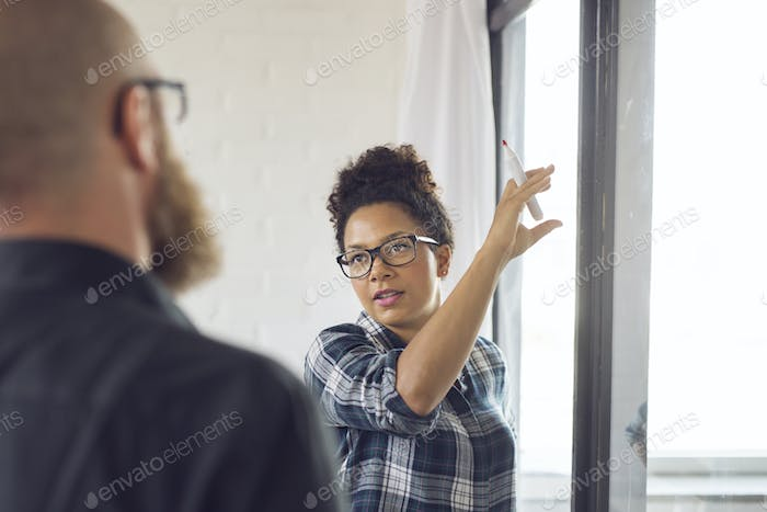 Office worker pointing at glass wall