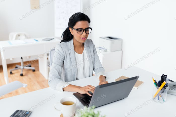 happy smiling businesswoman with laptop at office