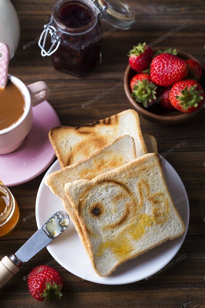 Breakfast with coffee, toasts, strawberry and jam on wooden background