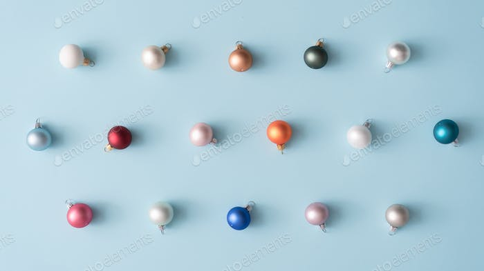Minimal colorful Christmas baubles in pastel colors. Holiday concept. Flat lay.