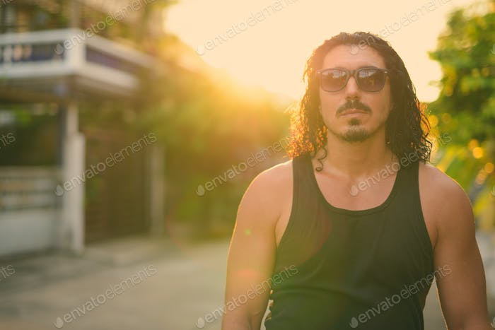 Handsome man with curly hair and mustache in the streets outdoors