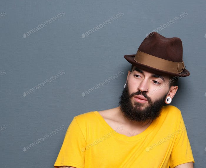 Young man with beard and piercings wearing hat