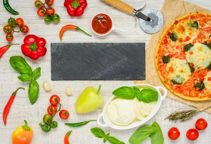 Pizza with Ingredients and Copy Space on a Dark Plate