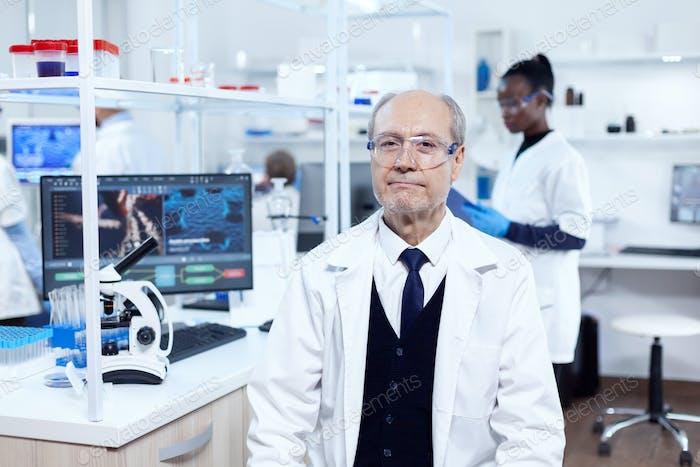 Старший химик-мужчина смотрит на камеру