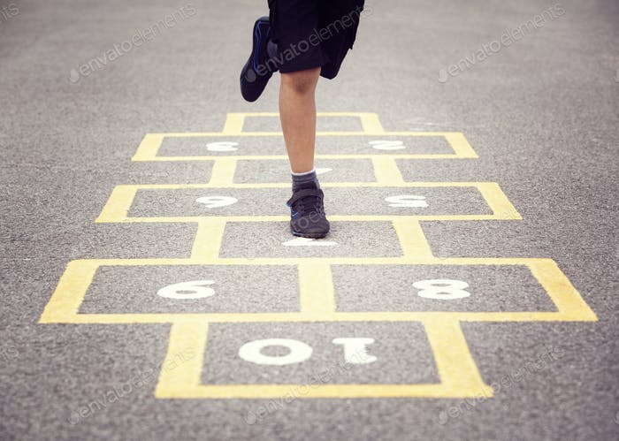 Child playing hopscotch on playground