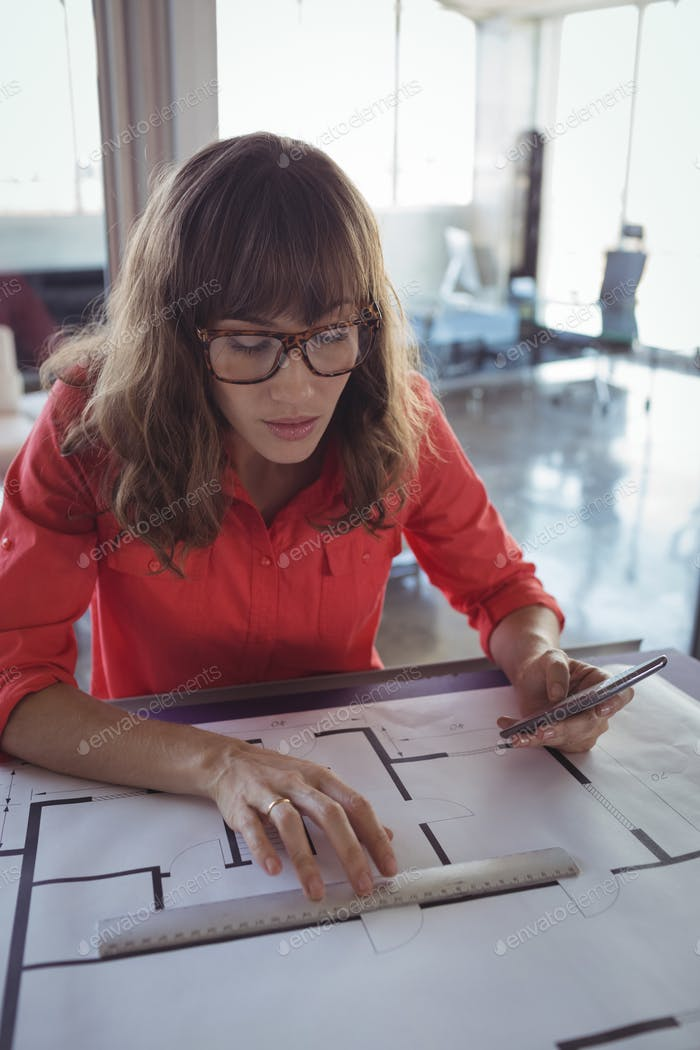 Female interior designer drawing on papers in office