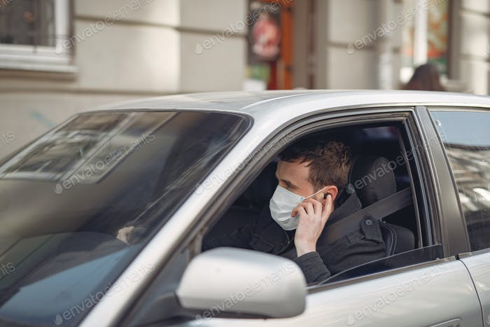 Man in a mask sitting in the car on the street