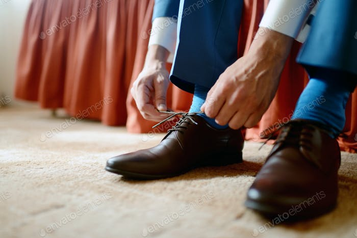 Groom is wearing shoes indoors