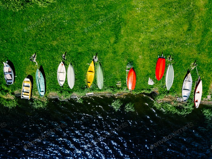 Aerial view of colorful  boats in a row on the shore of lake in Finland