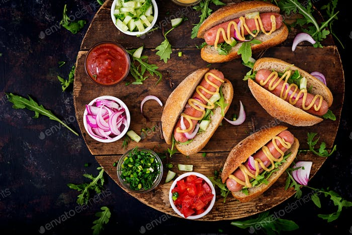 Hot dog with cucumber, tomato and red onion on wooden background. Top view. Flat lay