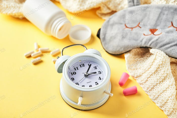 Sleeping mask, alarm clock, earplugs and pills on yellow. Healthy night sleep creative concept.