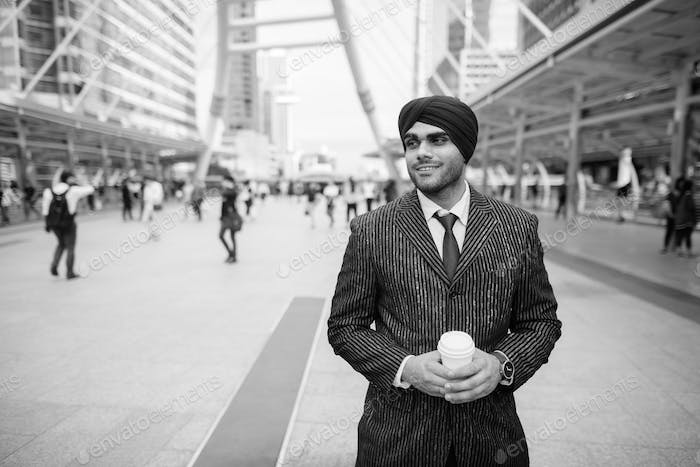 Happy young handsome Indian Sikh businessman wearing turban in the city