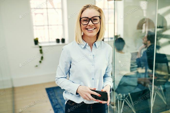 Selbstbewusste junge Geschäftsfrau hält ihr Handy in einem modernen Büro