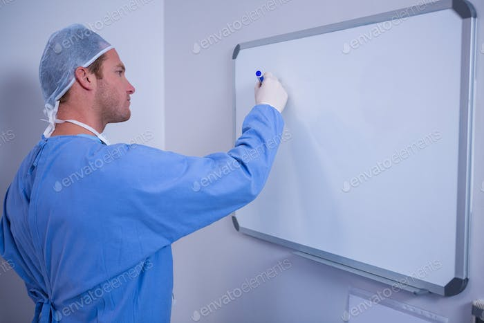 Male surgeon writing on whiteboard