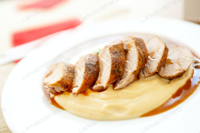 Close-up of grilled pork with mashed potatoes as main course at restaurant
