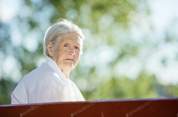 Senior woman sitting on bench in park