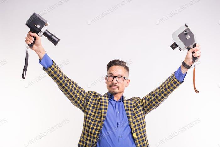 Technologien, Fotografieren und Menschen-Konzept - hübscher junger Mann mit zwei Retro-Kameras lächelnd