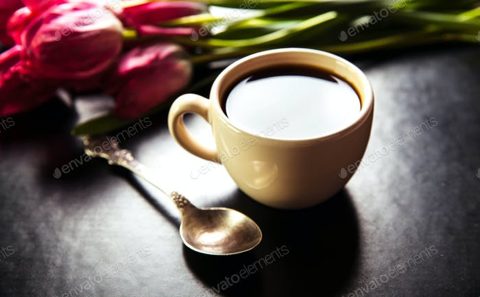 cup of coffee with tulip and book on black background