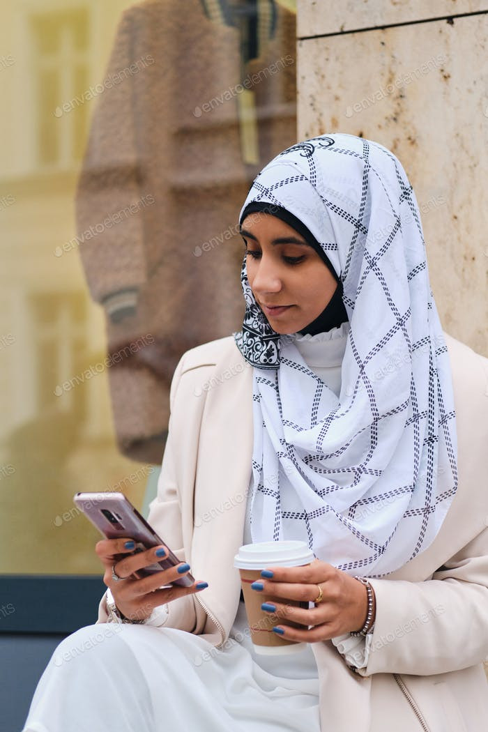 Young attractive Arabic woman in hijab intently using smartphone drinking coffee on city street