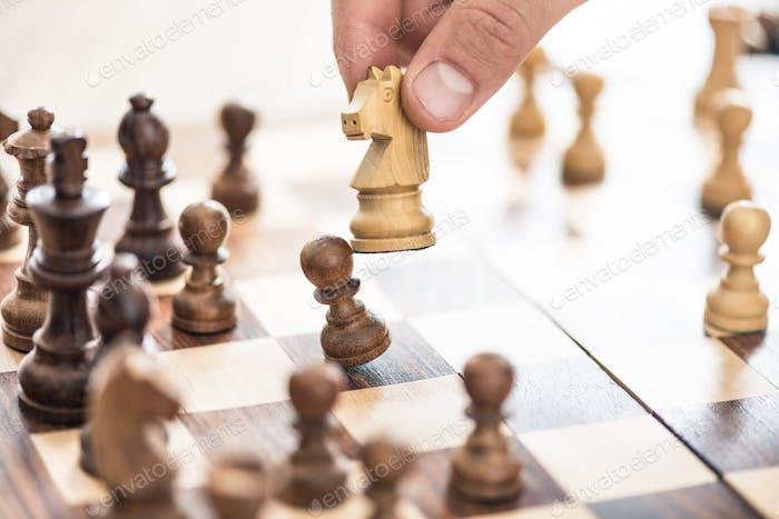 обрезанный выстрел человеческой руки, играющей в шахматы, селективный фокус