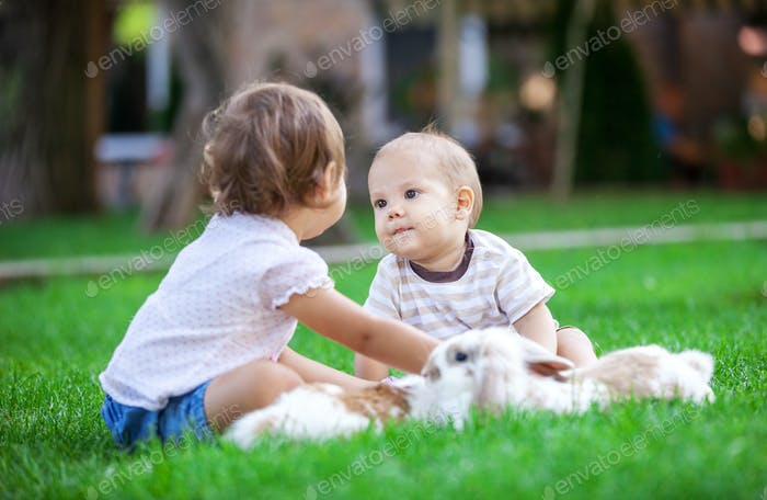 Baby boy and toddler girl playing with pet rabbits outdoors