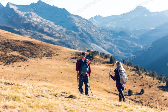 Two travel hikers with backpack walking while looking the landscape in the mountain. Back view.