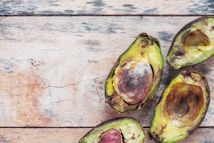 Avocado is rotten on wooden floor