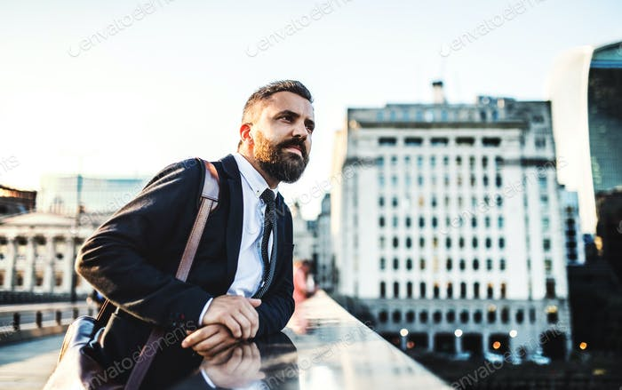 A hipster businessman standing on a bridge in the city, resting.