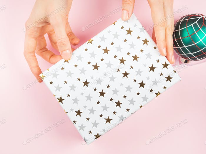Gift box and christmas ornament on pink, hands