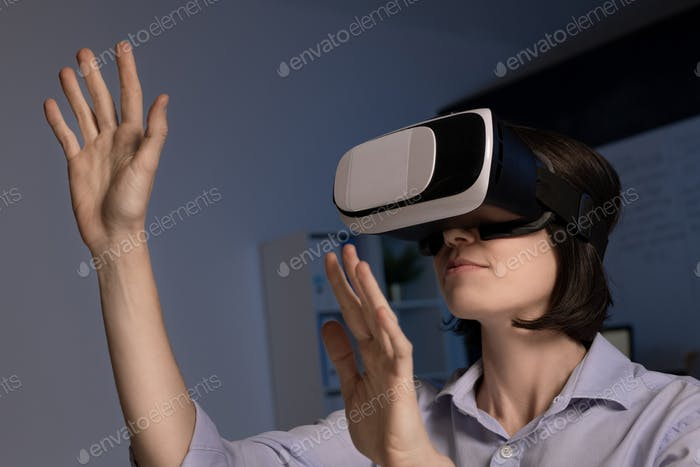 Contemporary employee with vr headset standing in front of virtual display