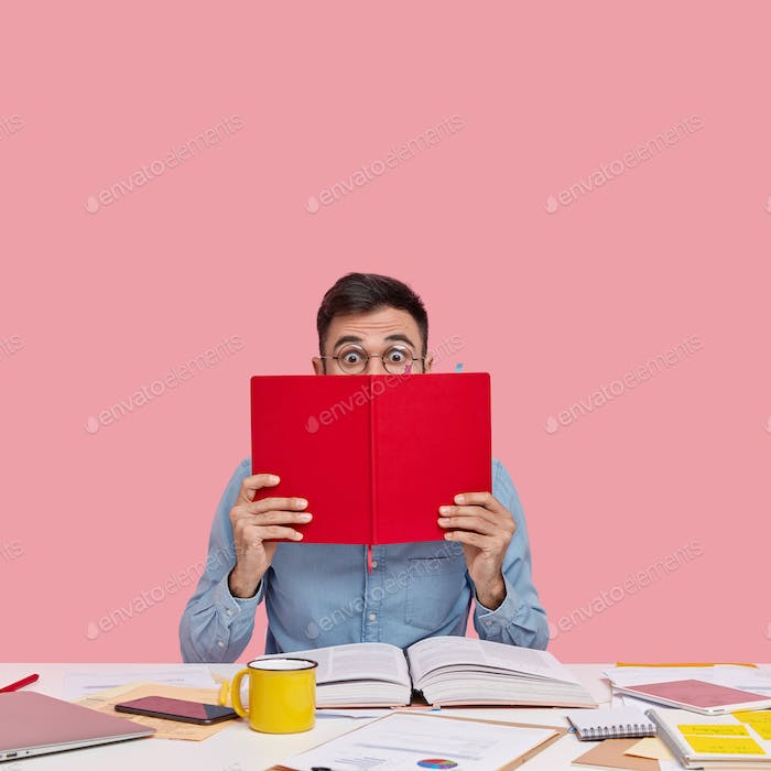 Indoor shot of astonished man covers half of face with red notepad, wears round spectacles, formal s